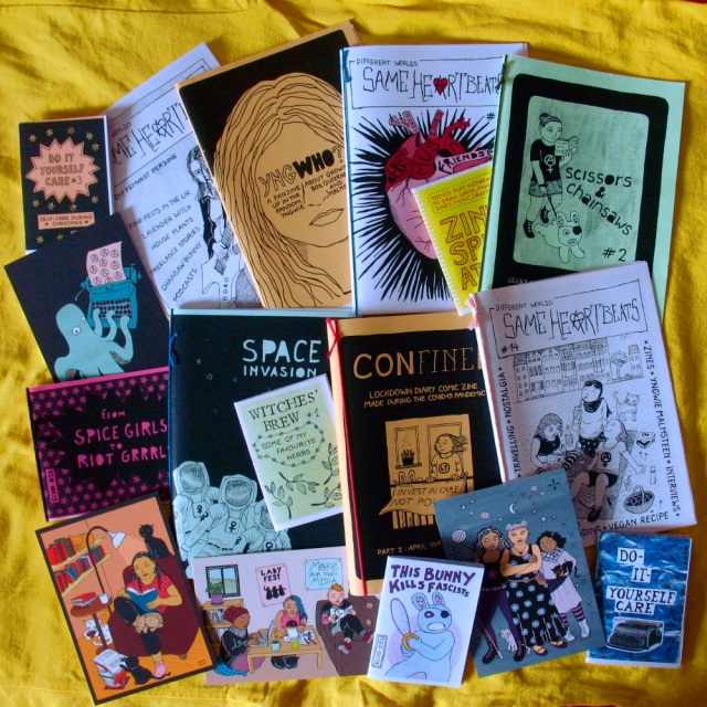 Zines, mini-zines and postcards displayed on yellow fabric. Zine titles are Do it yourself care, Yngwho, Same Heartbeats, Scissors & Chainsaws, Space Invasion, This Bunny Kills Fascists, From Spice Girls to Riot Grrrls, and Witches' Brew.