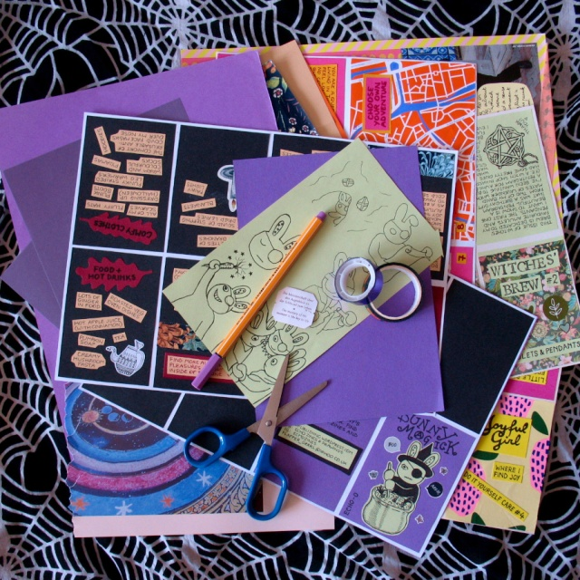 Collages and unfinished zine pages with purple washi tape, a purple pen and a scissors, on a spiderweb scarf as a background